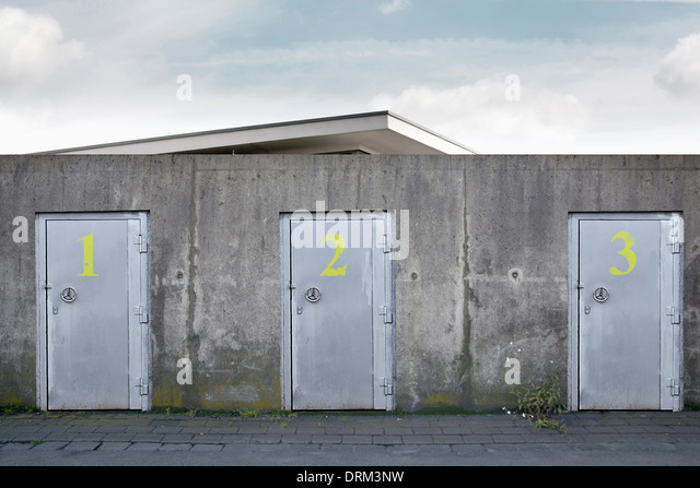 Building behind a wall with three safety doors, composing - Stock Image