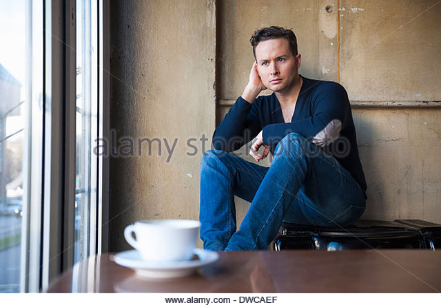Portrait of thoughtful mid adult man sitting in cafe - Stock Image