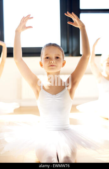 Graceful pretty little ballerina posing with raised arms in her white tutu in a bright sunlit dance studio as she - Stock Image