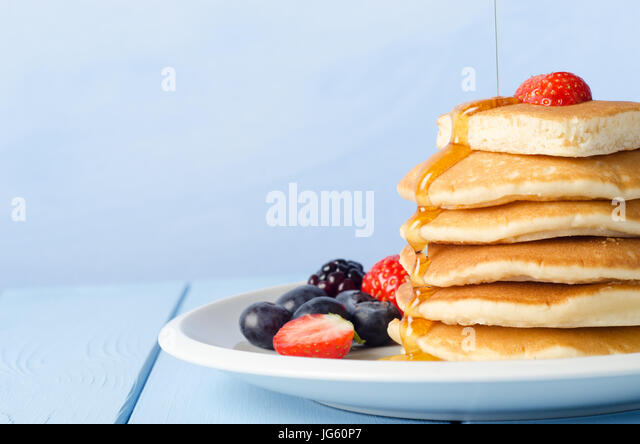 A stack of breakfast pancakes topped with a strawberry, standing on a white china plate, surrounded by Summer fruits, - Stock Image
