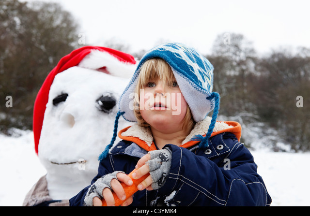 A boy with a carrot for a snowmans nose - Stock Image