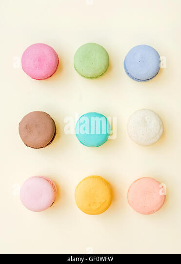 Sweet colorful French macaroon biscuits on pastel yellow background - Stock Image
