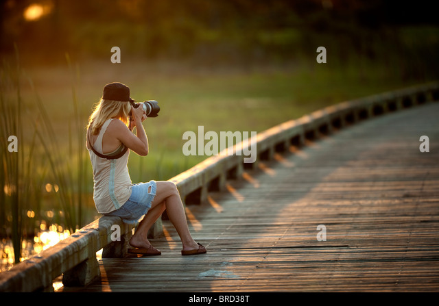Girl photographing at sunset - Stock Image