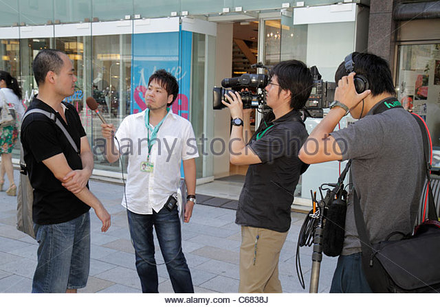 Tokyo Japan Ginza Chuo Dori Street Asian man men TV television media video camcorder crew reporter microphone interview - Stock Image
