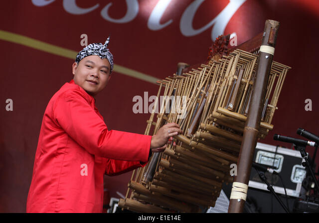 London, UK. 31 May 2014. A man is seen playing a tradition bamboo instrument, the Angklung Rack during Indonesia - Stock Image
