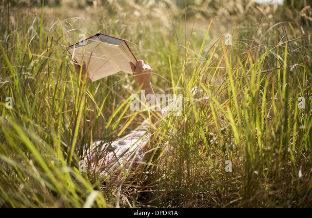 Woman lying in long grass reading book - Stock Image