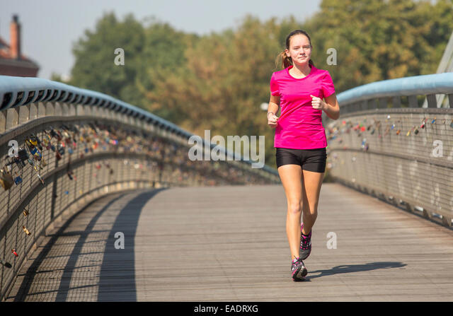 Young cute girl while jogging in the city. Healthy lifestyle. - Stock Image