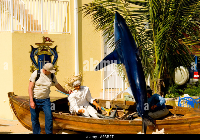 George Town Grand Cayman tourist with mock shark fishing boat  humor - Stock Image