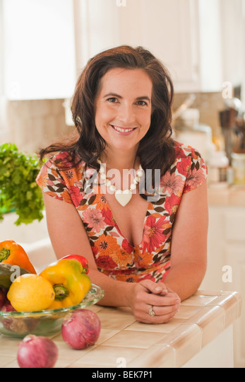 Portrait of a mid adult woman leaning on a kitchen counter and smiling - Stock-Bilder