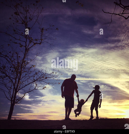 USA, California, Orange County, Father with sons at sunset - Stock Image