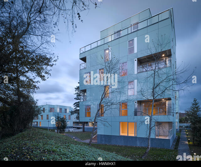 Dusk view of exterior showing walkway and lit interior. Dunluce Apartments, Ballsbridge, Ireland. Architect: Derek - Stock-Bilder
