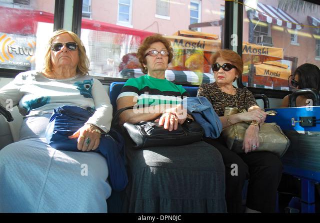 Miami Beach Florida public bus riders passengers Hispanic woman senior sitting - Stock Image