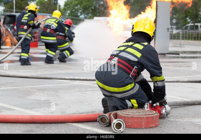 Firefighters spraying water in fire fighting training operation - Stock Image