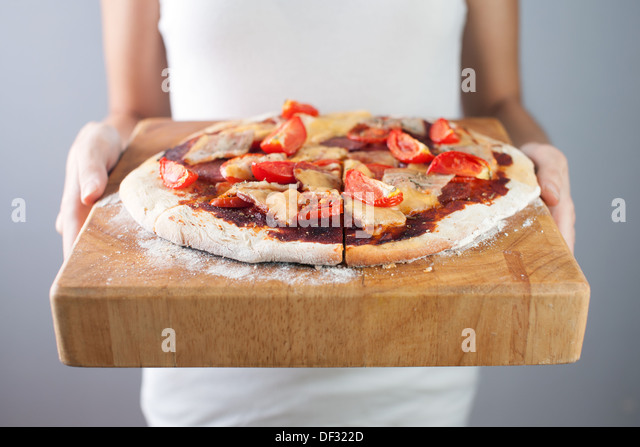 Woman's hands holds homemade pizza with tomato, bacon, salami and cheese. Wooden cutting board. - Stock Image