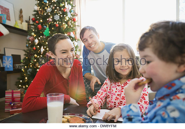 Family looking at boy eating Christmas cookie - Stock Image