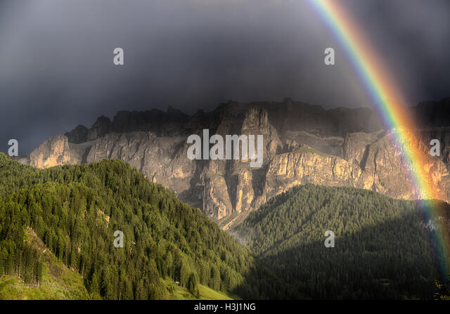 Rainbow after the thunderstorm over the hills and mountains of Selva di Val Gardena in a summer day, Trentino-Alto - Stock Image