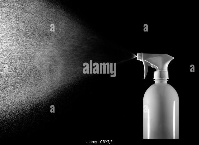 Spray bottle spraying water - Stock Image