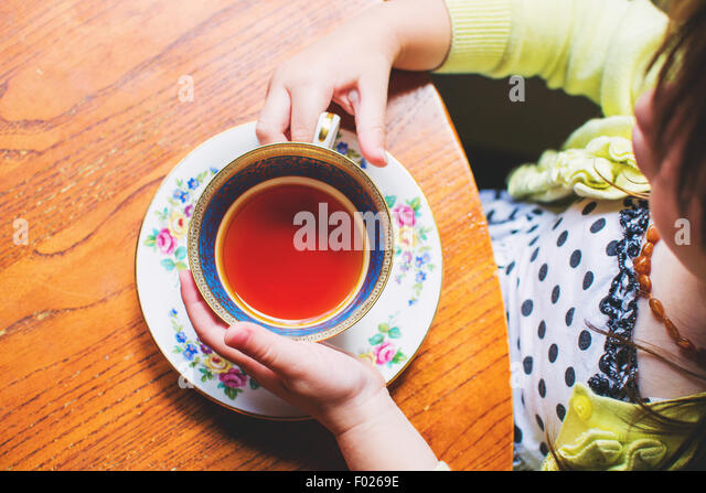 Overhead view of a girl sitting at table holding a teacup - Stock Image