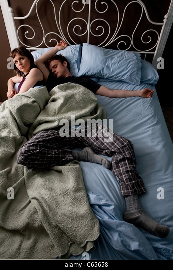 Young man asleep, woman squashed to the edge of bed - Stock Image