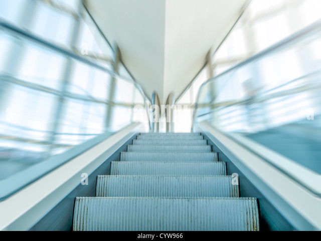 Close view of moving staircase or escalator inside modern business centre. Empty escalator with blue glass handrails - Stock Image