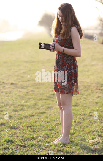 Young woman on a meadow with nostalgic camera - Stock-Bilder