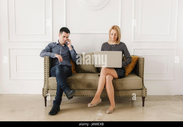 Middle Eastern couple sitting on sofa using technology - Stock-Bilder