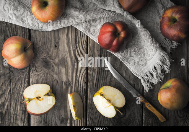 Red apples and apple halves on a wooden table horizontal - Stock Image