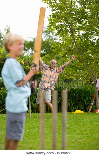 Boy 10-12 playing cricket with father - Stock Image