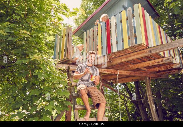 Portrait of father and two sons painting tree house - Stock Image