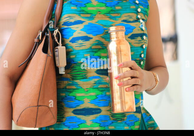 Woman holding copper flask - Stock Image