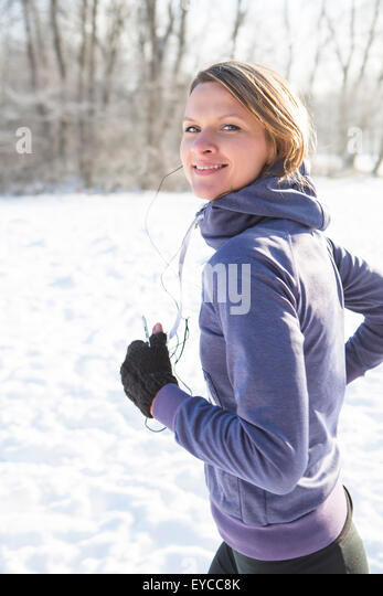 Young woman jogging in snow - Stock Image
