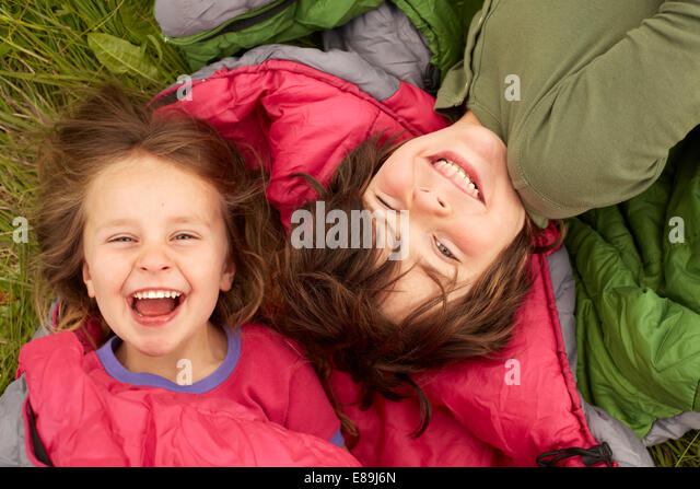 Laughing kids laying on sleeping bags - Stock Image