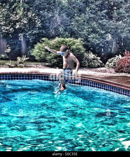 Boy takes cannonball jump into swimming pool - Stock-Bilder
