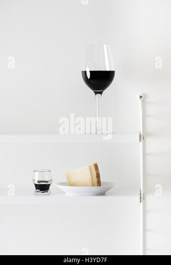 Red wine, parmesan cheese and balsamic vinegar on bookshelf. Food still life. - Stock-Bilder