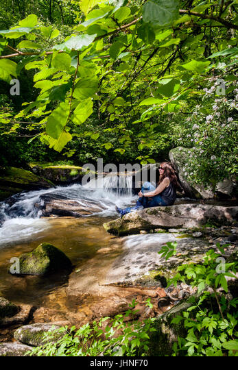 Young woman sitting by Davidson River in Pisgah National Forest - near Brevard, North Carolina, USA - Stock Image