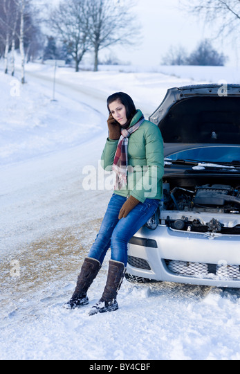 Winter car breakdown - woman call for help, road assistance - Stock Image
