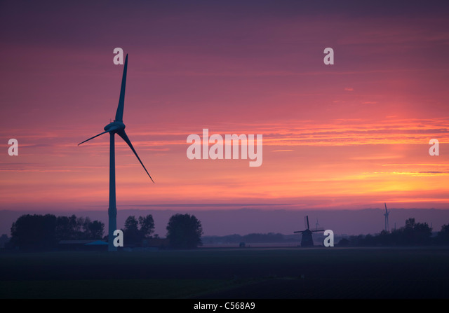 The Netherlands, Castricum, Windturbines and windmill at dawn. - Stock Image
