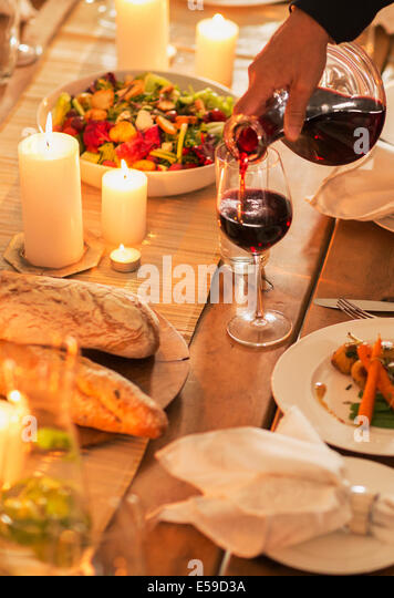 Woman pouring wine at dinner party - Stock Image