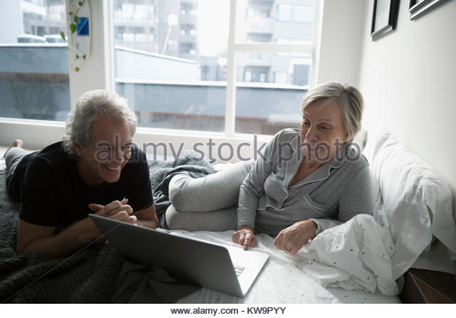 Smiling senior couple in pajamas relaxing,using laptop on bed in urban apartment - Stock Image