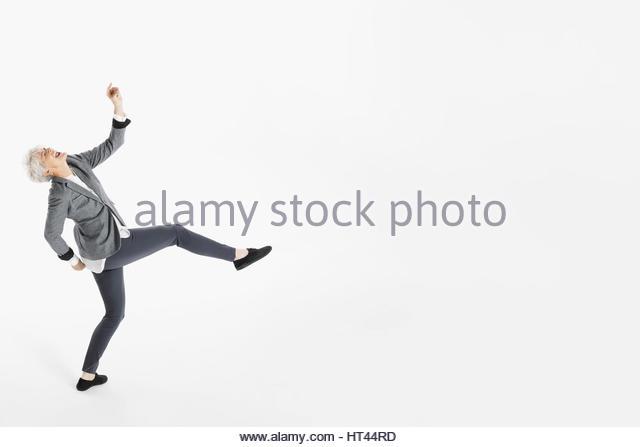Playful, energetic senior woman dancing against white background - Stock-Bilder