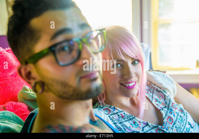 Portrait of funky couple reclining on bed - Stock-Bilder