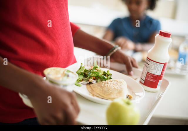 Black students eating lunch in school cafeteria - Stock Image