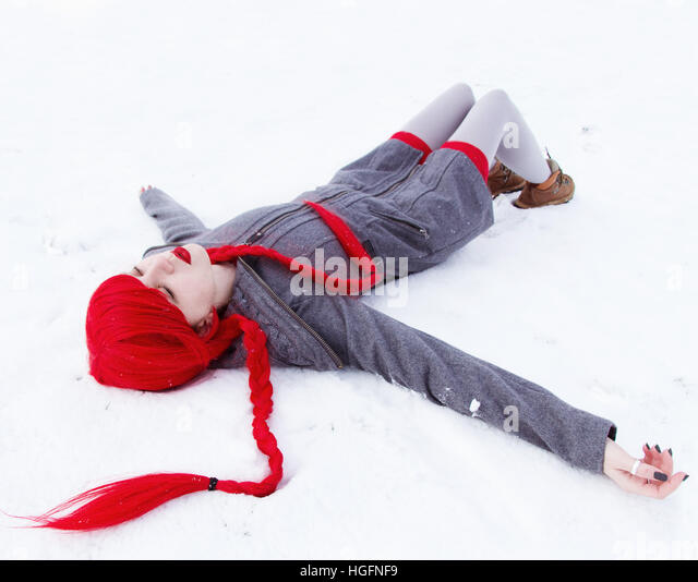 Young woman with winter clothes and red hair lying on snow - Stock Image