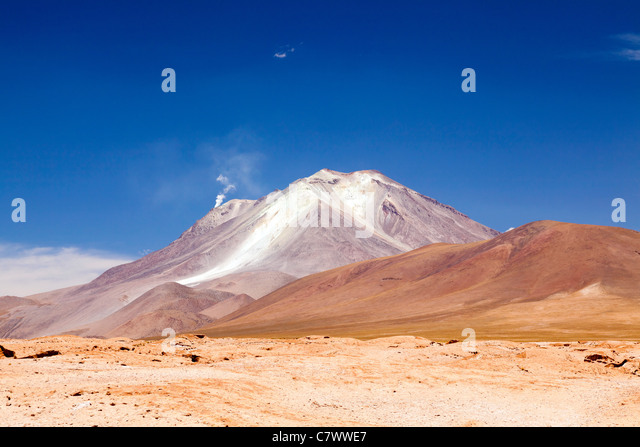 The stunning scenery between San Pedro de Quemez and Ojo de Perdiz, Bolivia, with steam rising from a volcano in - Stock Image