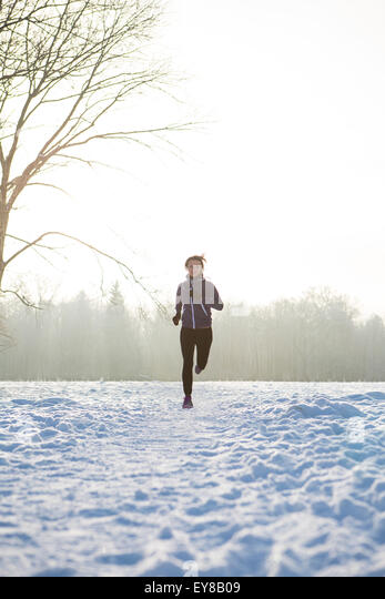 Young woman jogging in winter landscape - Stock Image