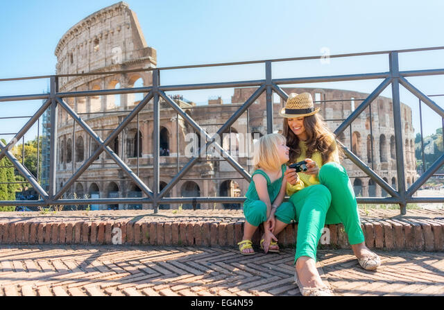 Mother and baby girl sitting in front of colosseum in rome, italy - Stock Image