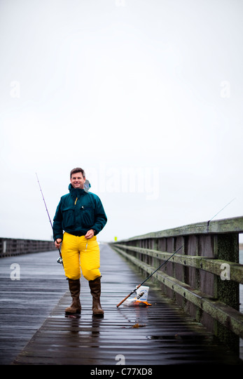 A portrait of man fishing off the pier on a rainy day. - Stock Image