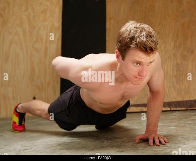 Mid adult male doing one armed push ups in gym - Stock Image