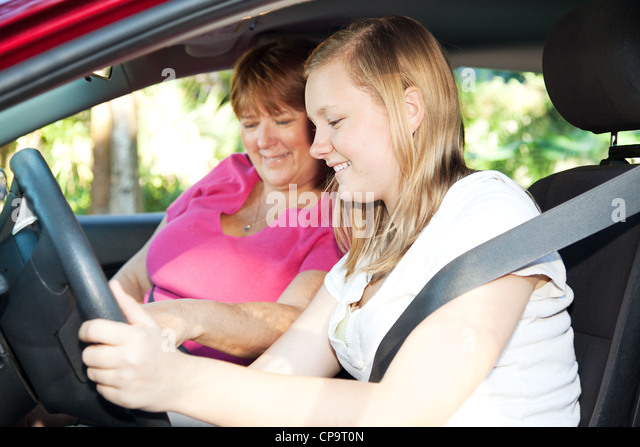 Teenage girl eager to start a driving lesson with her mother or an instructor. - Stock Image