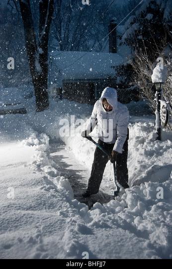 Shoveling Snow At Night While Snowing, Pennsylvania, USA - Stock Image